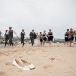 photo wedding party running on charlevoix city beach